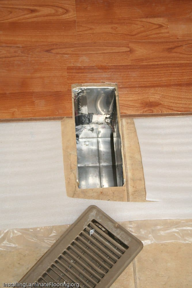 Laminate trimmed to fit around mobile home floor duct